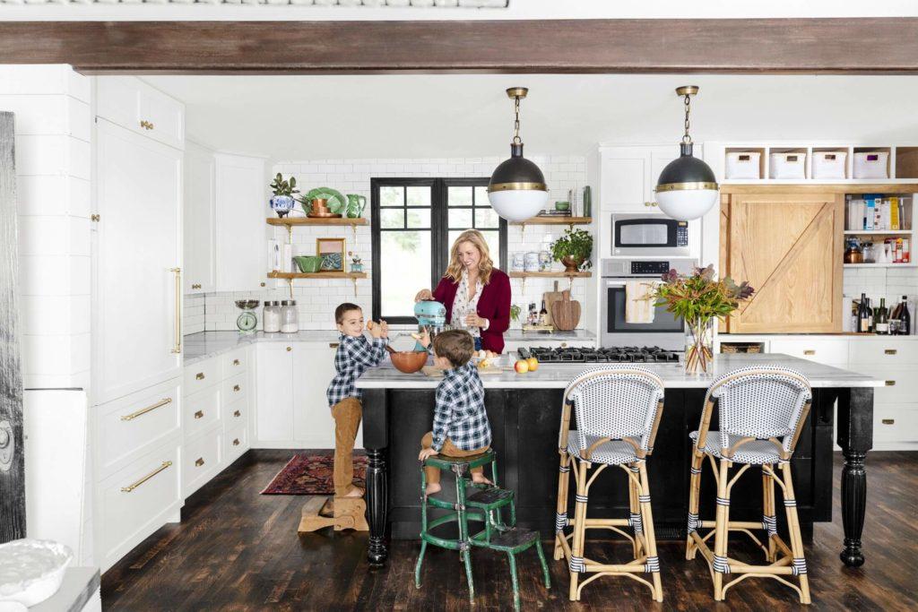 Family standing around kitchen island bench with kitchen pendant lights